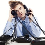 21717787 - young man sitting in the office and answering several phones at the same time